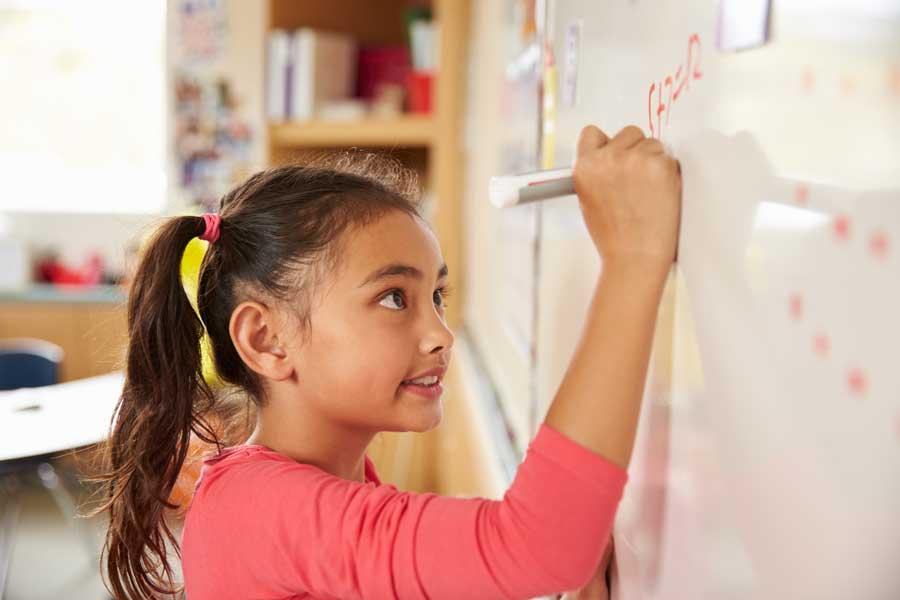 girl solving math problems on whiteboard